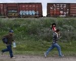 A Salvadoran father carries his son while running next to another immigrant as they try to board a train heading to the Mexican-U.S. border, in Huehuetoca, near Mexico City.