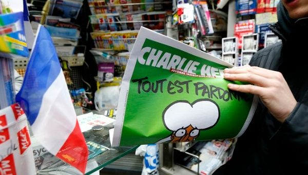 "A man holds a 2015 issue of satirical French weekly Charlie Hebdo entitled ""Tout est pardonne"" (""All is forgiven""), which shows a caricature of Prophet Mohammad."