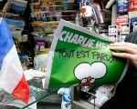 A man holds a 2015 issue of satirical French weekly Charlie Hebdo entitled