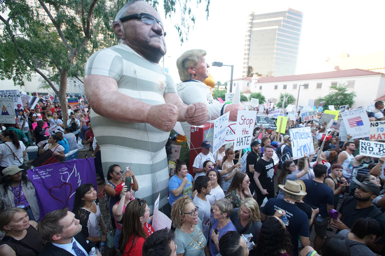 Effigies of Joe Arpaio and Donald Trump being carried by anti-Trump protesters