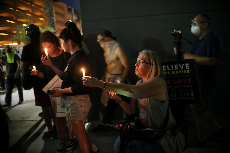 Anti-Trump protesters hold candles as the rally extends into the evening