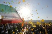 Supporters display Hezbollah and Iranian flags as they listen to Nasrallah during a rally marking the 11th anniversary of the end of Hezbollah's 2006 war with Israel.
