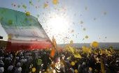 Supporters display Hezbollah and Iranian flags as they listen to Nasrallah during a rally marking the 11th anniversary of the end of Hezbollah