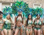 Costumed masqueraders pose before taking to the streets as part of Notting Hill Carnival.
