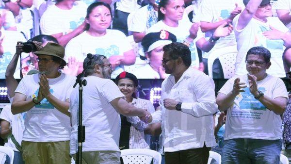 """""""Timochenko"""" (2i) estrecha la mano de """"Iván Márquez"""" (2d) tras la declaración política de la Décima Conferencia Nacional Guerrillera."""