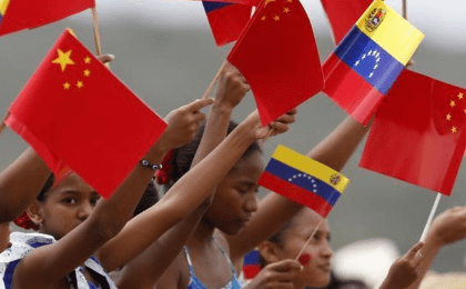 Venezuelan children wave flags as they welcome China