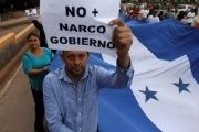 Demonstrators march against the reelection bid of Honduran president.