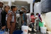 Children stand in line for water at a school in Sanaa, Yemen