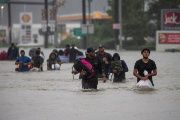 Residents wade through flood waters from Tropical Storm Harvey while evacuating their neighborhood in east Houston, Texas, U.S. August 28, 2017.