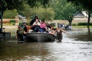 People evacuate by boat from the Hurricane Harvey floodwaters in Houston, Texas, on August 29, 2017.