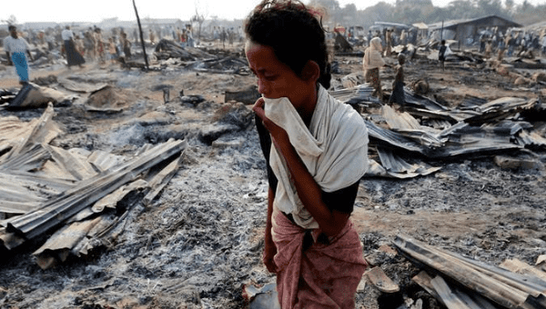 A woman walks among debris after fire destroyed shelters at a camp for internally displaced Rohingya Muslims near Sittwe, Myanmar, May 3, 2016.