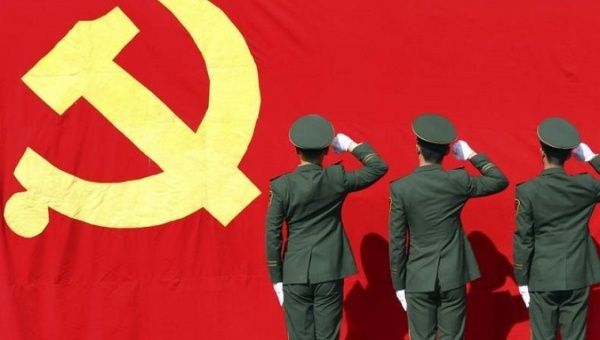 Paramilitary police raise fists to the Communist Party of China flag ahead of a National Congress.
