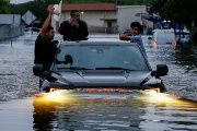Residents use a truck to navigate through floodwaters from Harvey in Houston, Texas.
