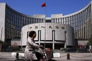 A woman rides past the headquarters of the People's Bank of China in Beijing, April 3, 2014