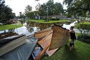 A woman piles debris outside of her home that was flooded by Tropical Storm Harvey in Orange, Texas.