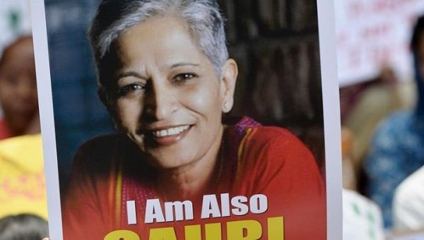 A protester holds a sign with journalist Gauri Lankesh at a rally following her murder on Tuesday night.