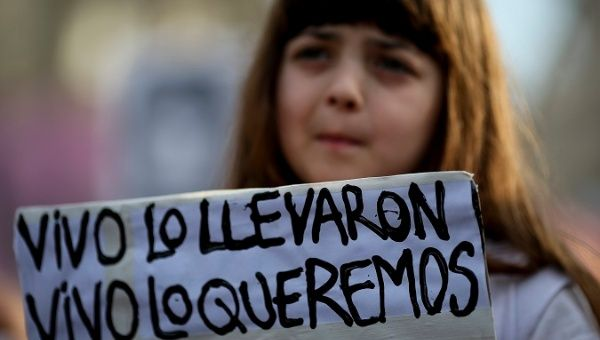 "A woman holds a sign that reads, ""They took him alive, we want him back alive,"" during a protest in Buenos Aires."
