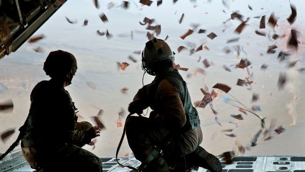 A U.S. Army psychological specialist with and a U.S. Marine Corps load master watch leaflets fall off of a KC-130 Super Hercules over Afghanistan. (FILE)