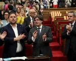 Catalonia's President Carles Puigdemont stands with deputies after voting for an Oct. 1 independence referendum in the Catalan Parliament in Barcelona, Sept. 6, 2017.
