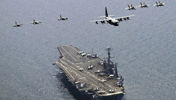 A U.S. Marine Corps C-130 Hercules aircraft leads a formation over the aircraft carrier USS George Washington in the East Sea of Korea.