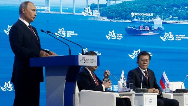 Russian President Vladimir Putin (L) delivers a speech with South Korean President Moon Jae-In (R) seated during a session of the Eastern Economic Forum in Vladivostok, Russia Sept. 7, 2017.
