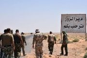 Members of the Syrian Arab Army stand at the entrance to the area around Deir ez-Zor just before breaking the seige. The writing in Arabic reads: 'Welcome to Deir Ezzor.