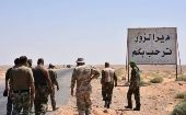 Members of the Syrian Arab Army stand at the entrance to the area around Deir ez-Zor just before breaking the seige. The writing in Arabic reads: