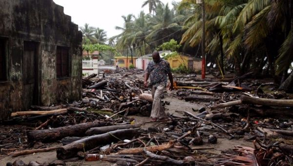 A man walks among debris off the northern coast of the Dominican Republic, in Nagua.
