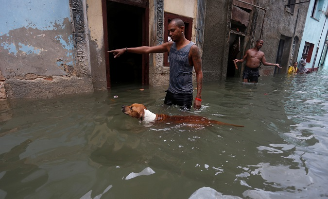 A man gestures to his dog on a flooded street in Havana