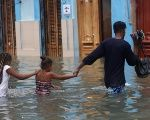 A man and two children wade through a flooded street, after Hurricane Irma, in Havana