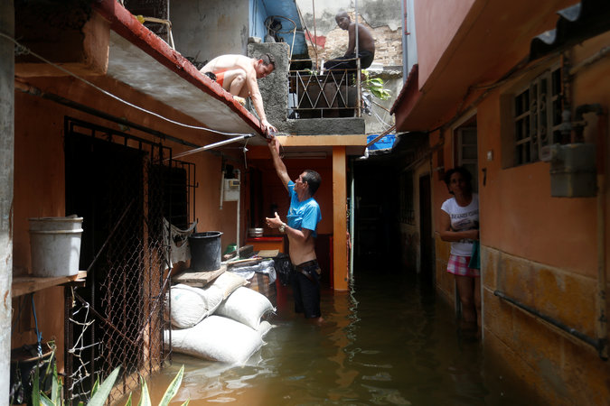 A man passes a drink to a neighbour while standing in the flooded passage of a block of flats