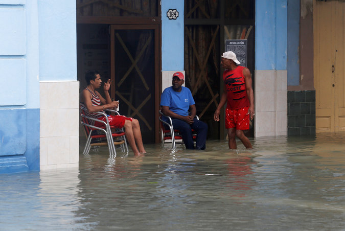 People sit in a flooded street