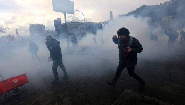 Police fire teargas at Chileans observing the anniversary of the Pinochet coup.