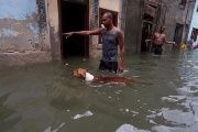 A man gestures to his dog on a flooded street in Havana.