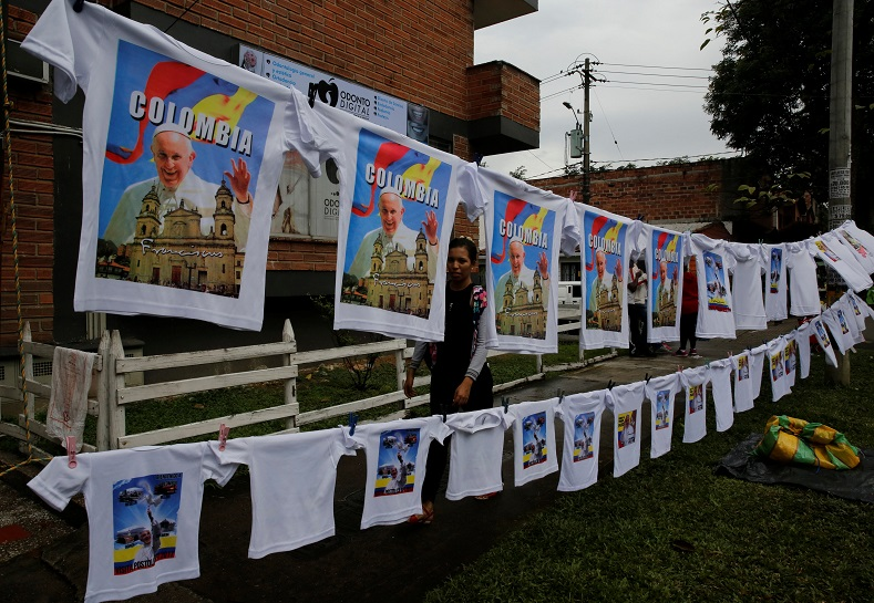 A woman sells T-shirts with images of the pope as people arrive for a mass outside Olaya Herrera Airport, Medellin, Colombia, Sept. 9, 2017.