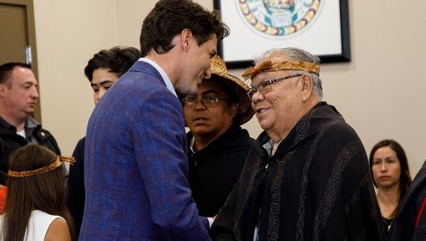 Canadian Prime Minister Justin Trudeau (L) meets a First Nations representative (R).