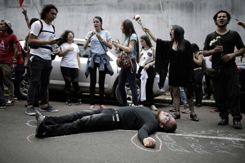 A student depicting a dead body lies on the ground at a protest in San Jose on September 12, 2017.