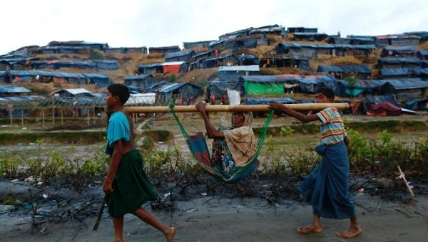 Rohingya refugee children carry an old woman near Balukhali makeshift refugee camp in Cox