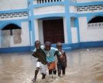 Haitian children walk in a flooded area after Hurricane Irma hit Fort Liberte, Haiti.