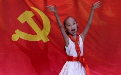 A schoolgirl performs in front of the flag of China