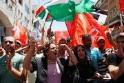 Palestinians wave Palestinian and Popular Front for the Liberation of Palestine (PFLP) flags.