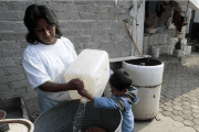 A mother and son fill a container with water collected from a public tap in Tecacalanco, on the outskirts of Mexico City.