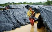 A Rohingya refugee woman and her child walk in floodwaters near makeshift shelters after heavy rains in Cox
