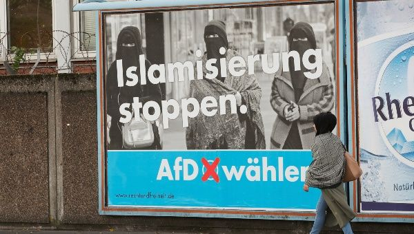 A woman with a headscarf walks past an election campaign poster of the anti-immigration party Alternative for Germany, AfD, in Marxloh, a suburb of Duisburg which local media said is populated mostly with people of Turkish migrant background, Germany, Sept. 13, 2017.