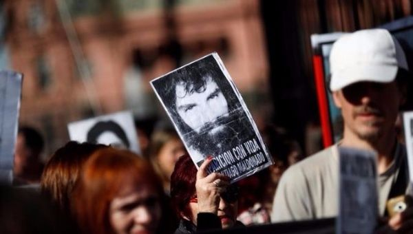 Demonstrators hold up an image of Santiago Maldonado.