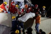 Mexican rescue workers remove the body of a child found inside the Enrique Rebsamen School in Coapa.