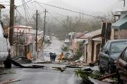 People survey the debris after the streets were hit by Hurricane Maria's winds and rains in Guayama, Puerto Rico