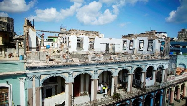 A man works at the terrace of a building in which the facade collapsed during the passage of Hurricane Irma in downtown Havana, Cuba.