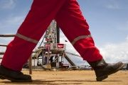 An oil worker walks past a drilling rig at an oil well operated by Venezuela's state oil company PDVSA in Morichal July 28, 2011.