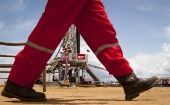 An oil worker walks past a drilling rig at an oil well operated by Venezuela